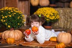Портрет прелестной усмехаясь девушки представляя с оранжевой тыквой в интерьере падения деревянном Стоковое Изображение RF