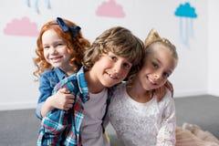 портрет прелестных счастливых детей усмехаясь на камере пока обнимающ Стоковые Фото