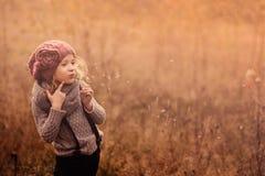 Портрет прелестной девушки ребенка с шариком дуновения в пинке связал шляпу и серый свитер в винтажных пастельных тонах Стоковая Фотография
