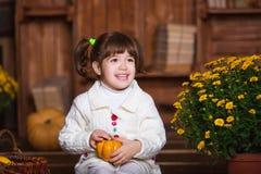 Портрет прелестной усмехаясь девушки представляя с оранжевой тыквой в интерьере падения деревянном Стоковые Изображения RF
