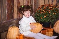 Портрет прелестной усмехаясь девушки представляя с оранжевой тыквой в интерьере падения деревянном Стоковые Фотографии RF