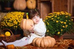 Портрет прелестной усмехаясь девушки представляя с оранжевой тыквой в интерьере падения деревянном Стоковая Фотография RF