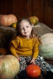 Портрет прелестной усмехаясь девушки представляя с оранжевой тыквой в интерьере падения деревянном отлично Стоковые Изображения RF
