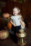 Портрет прелестной усмехаясь девушки представляя с оранжевой тыквой в интерьере падения деревянном отлично Стоковое фото RF