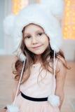 Портрет прелестной усмехаясь меховой шапки девушки ребенка нося Стоковые Изображения RF