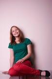 Портрет предназначенной для подростков девушки сидя на таблице Стоковая Фотография