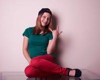 Портрет предназначенной для подростков девушки сидя на таблице Стоковые Фото