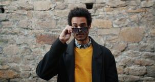 Портрет привлекательного Афро-американского студента принимая солнечные очки снаружи акции видеоматериалы