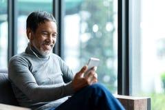 Портрет привлекательного зрелого азиатского человека выбыл с стильной короткой бородой используя музыку smartphone сидя или слуша стоковое изображение