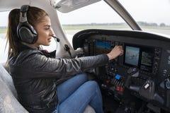 Портрет привлекательного пилота молодой женщины со шлемофоном в арене стоковые фото