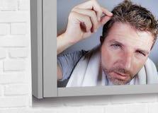 Портрет привлекательного потревоженного и, который отнесенного кавказского человека смотря зеркало ванной комнаты находя с серыми Стоковые Изображения