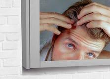 Портрет привлекательного потревоженного и, который отнесенного кавказского человека смотря зеркало ванной комнаты находя с серыми Стоковое фото RF