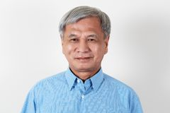 Портрет привлекательного старшего азиатского человека усмехаясь и смотря камеру в студии стоковое фото rf