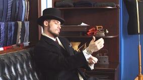 Портрет привлекательного человека в темном пальто и ультрамодном костюме внутри помещения портняжничает акции видеоматериалы