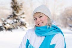 Портрет привлекательной белокурой усмехаясь девушки в снежном лесе Стоковые Фото