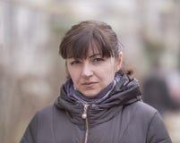 Портрет привлекательной девушки брюнета на запачканной предпосылке улицы, смотря камеру стоковая фотография rf