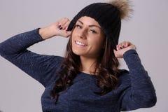 Портрет привлекательной женщины брюнет нося теплую шляпу и пуловер представляя на светлой предпосылке Стоковые Изображения RF