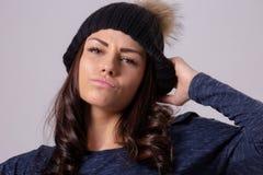 Портрет привлекательной женщины брюнет нося теплую шляпу и пуловер представляя на светлой предпосылке Стоковое Изображение