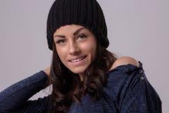 Портрет привлекательной женщины брюнет нося теплую шляпу и пуловер представляя на светлой предпосылке Стоковое Изображение RF