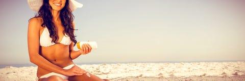 Портрет привлекательной женщины прикладывая сливк солнца пока сидящ на ее полотенце стоковые изображения