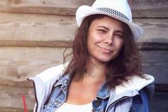Портрет привлекательной загоренной молодой женщины в ковбойской шляпе против деревянного обнести куртка джинсовой ткани красивейш стоковые изображения