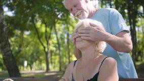Портрет привлекательной зрелой женщины сидя на стенде в парке Усмехаясь старший человек приходя вверх за ей и акции видеоматериалы