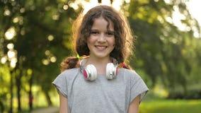 Портрет привлекательной кавказской маленькой девушки студента с красивыми глазами Брауна с наушниками Счастливый усмехаясь ребено сток-видео