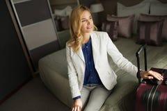 Портрет привлекательной коммерсантки сидя на кровати Стоковые Изображения