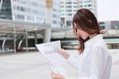 Портрет привлекательной молодой азиатской бизнес-леди анализируя диаграммы или обработку документов на внешнем офисе Стоковое Изображение RF