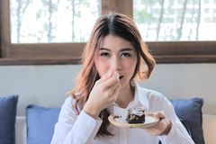 Портрет привлекательной молодой азиатской женщины с вилкой есть торт пирожного в кафе Стоковые Изображения RF