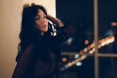 Портрет привлекательной молодой женщины в черном платье коктейля полагаясь на стене стоковое фото rf