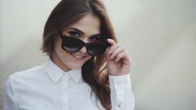 Портрет привлекательной молодой женщины усмехаясь на пляже извлекает солнечные очки крутые акции видеоматериалы