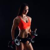 Портрет привлекательной молодой женщины фитнеса в sportswear делая разминку с гантелями на черной предпосылке Стоковое Изображение RF