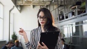 Портрет привлекательной молодой коммерсантки работая с печатными документами, делая некоторые примечания в тетради в офисе сток-видео