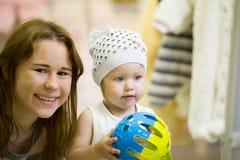 Портрет привлекательной молодой матери с ее дочерью на магазине одежд ` s детей Стоковое Изображение
