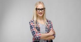 Портрет привлекательной прелестной белокурой девушки подростка в checkered одеждах в стеклах с оружиями пересек на серый цвет Стоковое фото RF