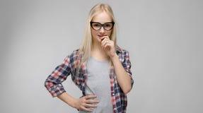 Портрет привлекательной сладостной прелестной белокурой девушки подростка в checkered одеждах в стеклах на серой предпосылке Стоковые Фото