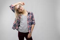 Портрет привлекательной сладостной прелестной белокурой девушки подростка в checkered одеждах в стеклах на серой предпосылке Стоковое Фото