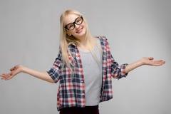 Портрет привлекательной сладостной прелестной белокурой девушки подростка в checkered одеждах в стеклах с открытыми оружиями на с Стоковая Фотография