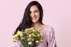 Портрет привлекательной темной с волосами женщины с нежной улыбкой, держит цветки, усмехается задушевно на камере, одетой в модно стоковые фотографии rf