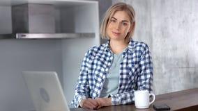 Портрет привлекательной усмехаясь молодой женщины фрилансера представляя во время деятельности используя ноутбук дома сток-видео