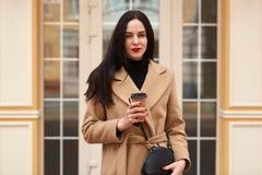 Портрет привлекательной элегантной женщины нося бежевое пальто и выпивая на вынос кофе пока идущ через улицу города Молодые стоковые фотографии rf