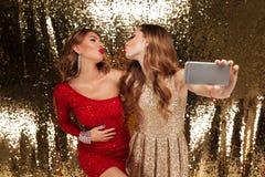 Портрет 2 привлекательных молодых женщин в sparkly платьях Стоковые Изображения