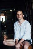 Портрет привлекательного молодого человека в белой рубашке сидя на стуле над предпосылкой темноты кафа стоковое фото