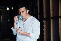 Портрет привлекательного молодого человека в белой рубашке сидя на стуле над предпосылкой темноты кафа Стоковые Фотографии RF