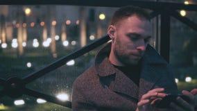 Портрет привлекательного молодого человека сидя в городе вечера и smartphone пользы Красивый мужчина просматривает интернет акции видеоматериалы