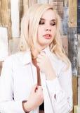 Портрет привлекательной белокурой девушки стоя на деревянной предпосылке стены Она имеет голубые глазы и одетая в рубашке ` s чел Стоковая Фотография RF