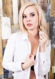 Портрет привлекательной белокурой девушки стоя на деревянной предпосылке стены Она имеет голубые глазы и одетая в рубашке ` s чел Стоковая Фотография