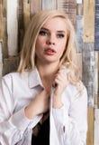 Портрет привлекательной белокурой девушки стоя на деревянной предпосылке стены Она имеет голубые глазы и одетая в рубашке ` s чел Стоковые Фотографии RF