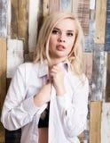 Портрет привлекательной белокурой девушки стоя на деревянной предпосылке стены Она имеет голубые глазы и одетая в рубашке ` s чел Стоковое Фото